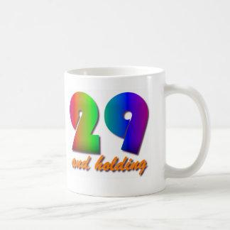 29 y el sostenerse taza de café