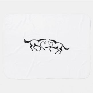2 caballos del dibujo lineal se encuentran a una mantita para bebé