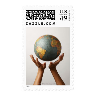 2 hands poised under moving globe postage stamps