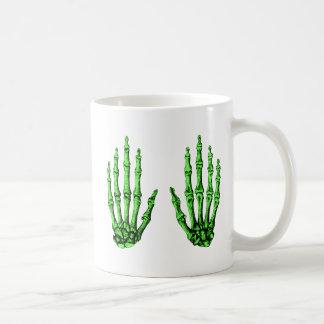 2 manos suben de color verde oscuro tazas de café