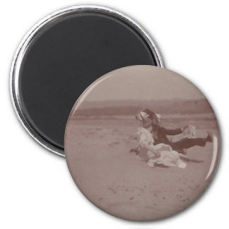 2 people at beach losing hats 2 inch round magnet