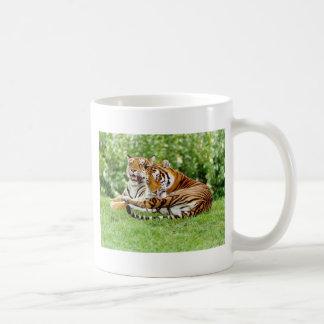 2 tigers resting on the grass coffee mug