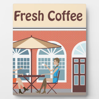 2 Women drinking coffee at a cafe outside Plaque