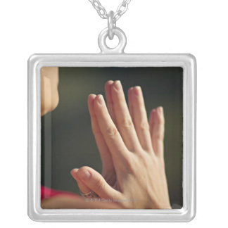 33 year old woman sits in meditation on a cliff square pendant necklace
