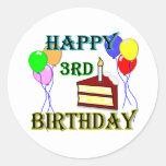 3ro cumpleaños feliz con la torta, los globos y la pegatina redonda