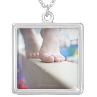 6-7 year old girl slowly walks across balance silver plated necklace