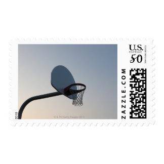 A basketball backboard hoop and net. Clear blue Postage