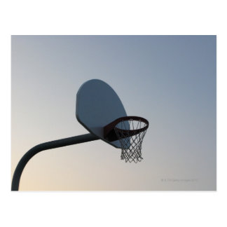 A basketball backboard hoop and net. Clear blue Postcard