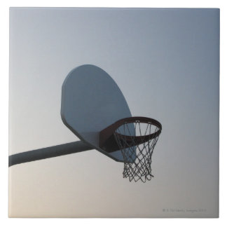 A basketball backboard hoop and net. Clear blue Tile
