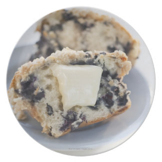 A blueberry muffin with butter party plates