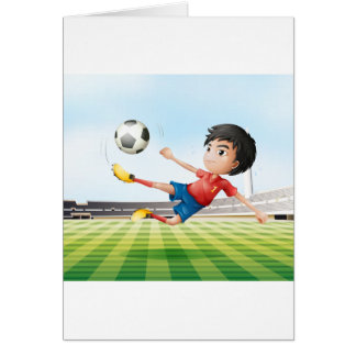 A boy playing soccer in the soccer field greeting card