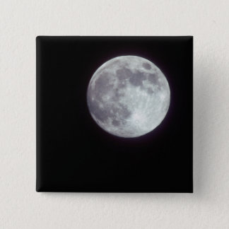 A bright full moon in a black night sky. button