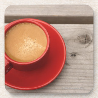A bright red cup of espresso coffee on a picnic beverage coaster