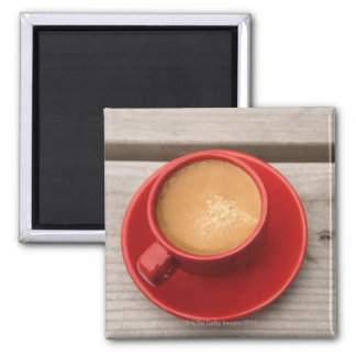 A bright red cup of espresso coffee on a picnic magnet
