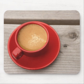 A bright red cup of espresso coffee on a picnic mouse pad