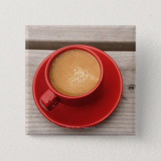 A bright red cup of espresso coffee on a picnic pinback button