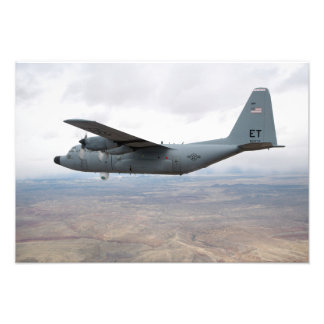 A C-130 Hercules soars through the sky Photo Print