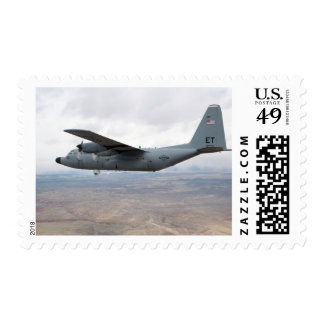 A C-130 Hercules soars through the sky Postage
