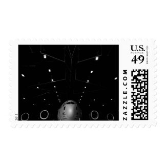 A C-17 Globemaster III sits in a hangar Postage Stamp