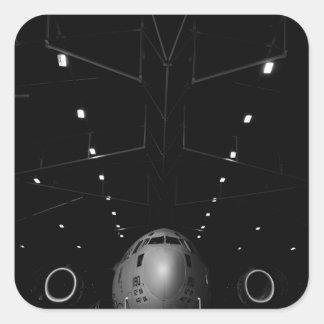 A C-17 Globemaster III sits in a hangar Square Sticker