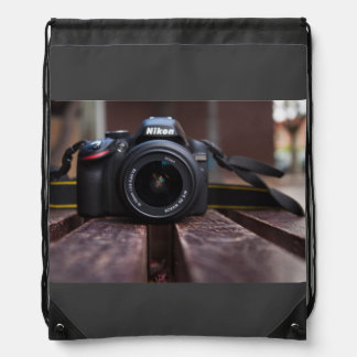 A camera on a table drawstring bag