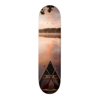 A canoe rests on the shore of Pawtuckaway Lake Skateboard Deck