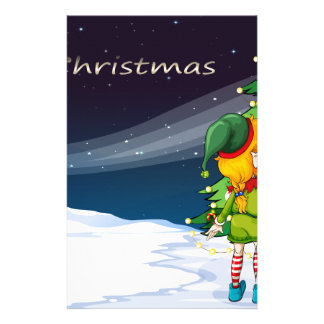 A card with an elf facing the christmas tree stationery