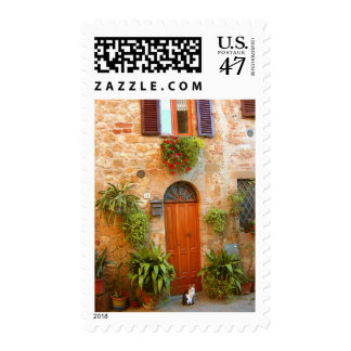 A cat seeks entrance to home in Pienza, Italy. Postage