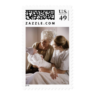 a caucasian mother shows her new baby to her own stamp