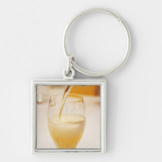 A champagne glass flute being filled with Gosset Silver-Colored Square Keychain