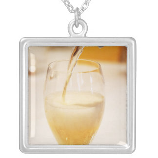 A champagne glass flute being filled with Gosset Square Pendant Necklace
