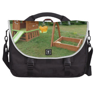 A child s playing equipment in a green location commuter bag