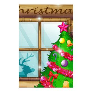 A christmas tree near the window stationery