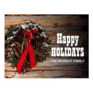 A Christmas wreath on a cabin wall Postcard