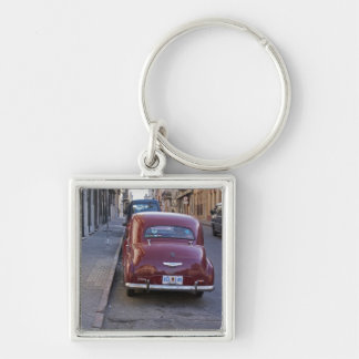 A classic old red Peugeot car parked on a street Keychain