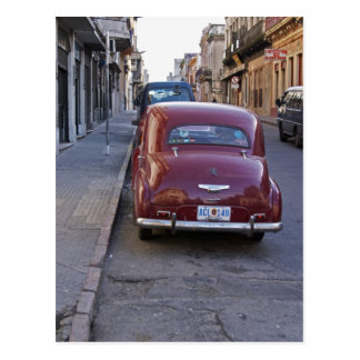 A classic old red Peugeot car parked on a street Postcard