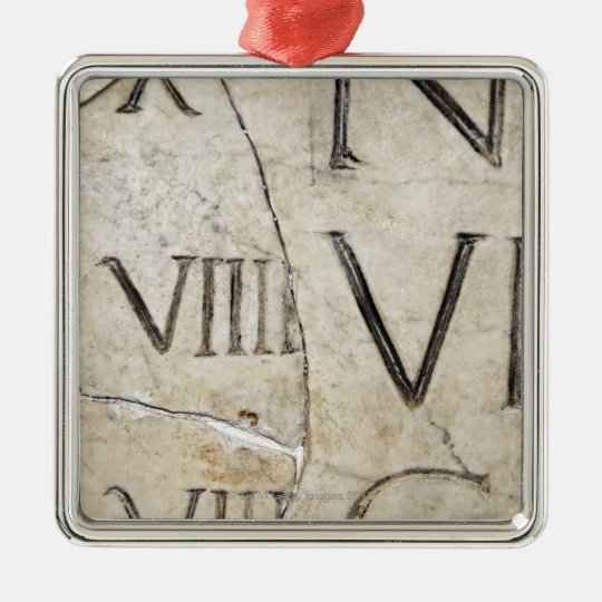 A close-up of ancient Roman letters on marble. Metal Ornament