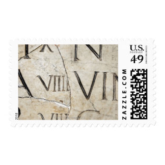 A close-up of ancient Roman letters on marble. Postage