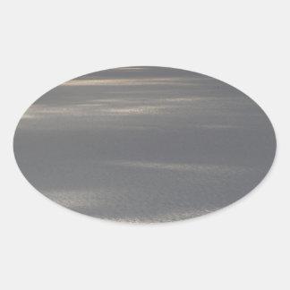 A cloudy sea and a setting sun oval sticker