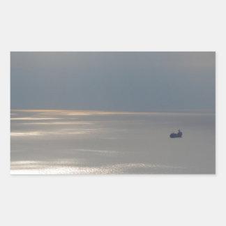 A cloudy sea and a setting sun rectangular sticker