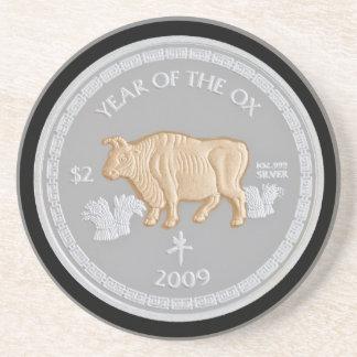 A commemorative silver coin drink coaster
