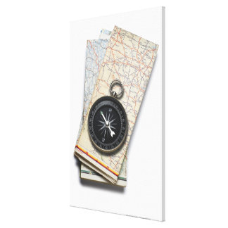 A compass sitting on a stack of folded road maps canvas print