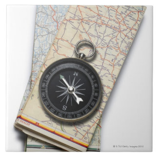 A compass sitting on a stack of folded road maps ceramic tile