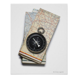 A compass sitting on a stack of folded road maps poster