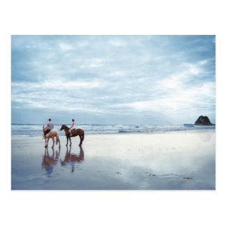 A couple riding horses on Parkiri beach in New Postcard