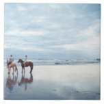 A couple riding horses on Parkiri beach in New Tile