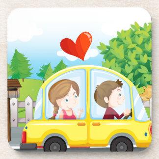 A couple riding on a yellow car coaster