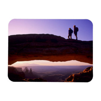 A couple watches sunrise from atop Mesa Arch in Magnet