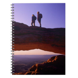 A couple watches sunrise from atop Mesa Arch in Notebook