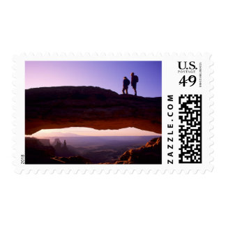 A couple watches sunrise from atop Mesa Arch in Postage Stamp
